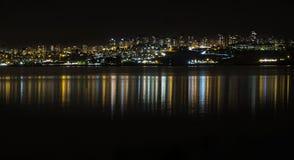 一个城市视图与反射的夜在水 库存图片