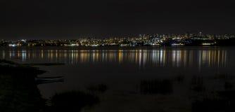 一个城市视图与反射的夜在水 免版税库存照片