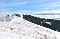 一个塔和一个小的房子多雪的小山的 免版税库存图片