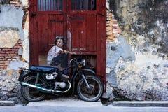 一个墙壁上的'男孩的全视图自行车的 免版税库存图片