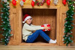 一个壁炉的圣诞节孩子与一个红色礼物盒 免版税库存图片