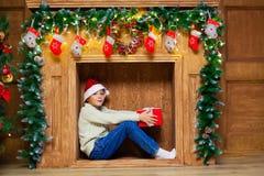 一个壁炉的圣诞节孩子与一个红色礼物盒 库存照片