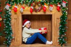 一个壁炉的圣诞节孩子与一个红色礼物盒 免版税库存照片