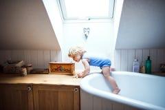 一个处境危险的小孩男孩在卫生间里 库存图片