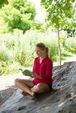 读一个夏天的微笑的20s女孩预定在树下 免版税图库摄影