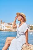 一个夏天礼服和帽子的美丽的女孩在背景老城市欧洲附近的海滨 地中海,锡切斯 免版税库存照片