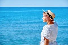 一个夏天礼服和帽子的美丽的女孩在背景老城市欧洲附近的海滨 地中海,锡切斯 库存图片