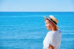 一个夏天礼服和帽子的美丽的女孩在背景老城市欧洲附近的海滨 地中海,锡切斯 库存照片