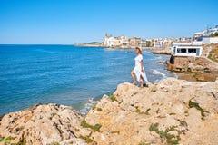 一个夏天礼服和帽子的美丽的女孩在背景老城市欧洲附近的海滨 地中海,锡切斯 免版税库存图片