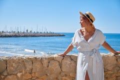 一个夏天礼服和帽子的美丽的女孩在背景老城市欧洲附近的海滨 地中海,锡切斯 图库摄影