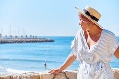 一个夏天礼服和帽子的美丽的女孩在背景老城市欧洲附近的海滨 地中海,锡切斯 免版税图库摄影