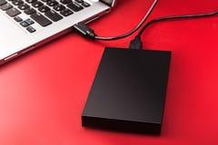 一个外在硬盘连接到膝上型计算机用在红色背景的一usb缆绳 库存图片