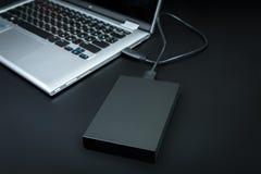 一个外在硬盘连接到膝上型计算机用在黑背景的一usb缆绳 免版税库存图片