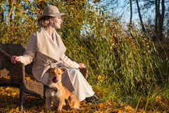 一个外套帽子和一件白色礼服的美丽的妇女步行的在秋天公园或森林 免版税库存照片
