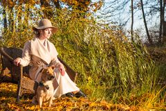 一个外套帽子和一件白色礼服的美丽的妇女步行的在秋天公园或森林 免版税图库摄影