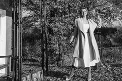 一个外套帽子和一件白色礼服的美丽的妇女步行的在秋天公园或森林 库存图片
