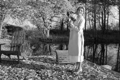 一个外套帽子和一件白色礼服的美丽的妇女步行的在秋天公园或森林 库存照片