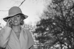 一个外套帽子和一件白色礼服的美丽的妇女步行的在秋天公园或森林 免版税库存图片