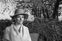 一个外套帽子和一件白色礼服的美丽的妇女步行的在秋天公园或森林 图库摄影