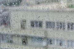 一个多层的在一块湿玻璃的背景的大厦和窗口的剪影与白色墙壁的与雨的斑纹 库存图片