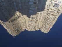 一个多层的房子的抽象反射一个水坑的与大海表面上的波纹 图库摄影