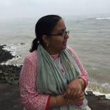 一个多岩石的海滩的一名年轻印地安妇女在Kunoor 免版税库存图片