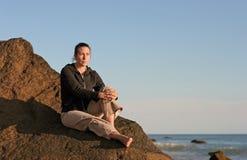 一个多岩石的海滩的体贴的女孩 免版税库存照片