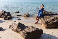 一个多岩石的海滩的年轻,亭亭玉立,白肤金发的妇女 免版税库存图片