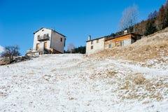 一个多雪的倾斜的两个山房子在蓝色早晨天空 免版税库存图片