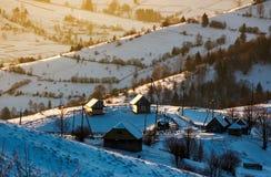 一个多雪的山坡的村庄在日出 库存照片