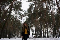 一个多雪的森林金发碧眼的女人的美丽的女孩有长的头发的 微笑 在降雪的前面 库存图片