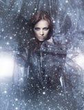 一个多雪的背景的一名新红头发人妇女 免版税图库摄影