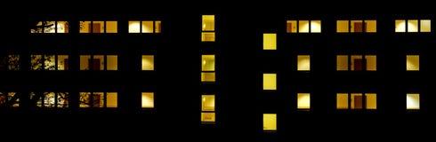 一个大厦的前面与被点燃的窗口的在晚上 免版税库存图片