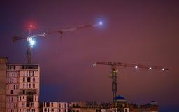 一个大厦的建筑由起重机的在晚上 库存图片