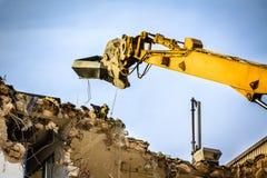 一个大厦的爆破与挖掘机的 库存照片
