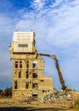 一个大厦的爆破与挖掘机的 库存图片