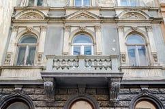一个大厦的门面与古老建筑学与窗口和一个阳台大阳台与专栏,样式和标志的在一个  免版税库存照片