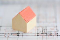一个大厦的建筑学计划与小模式房子的在图纸顶部 免版税库存照片