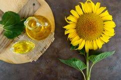 一个大向日葵,一个瓶在桌上的油 顶视图 免版税库存照片