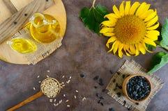 一个大向日葵,一个瓶油,在桌上的种子 顶视图 免版税库存图片