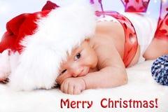 一个大圣诞老人帽子的婴孩 库存照片