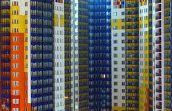 一个大大都会的蓝色红色白色高层居民住房睡觉区域,夜,灼烧的窗口 图库摄影
