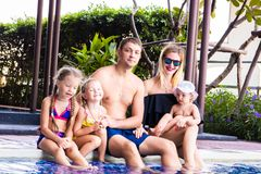 一个大家庭由在别墅的水池坐 妈妈、爸爸和三个女儿 幸福家庭,大的概念 免版税库存图片