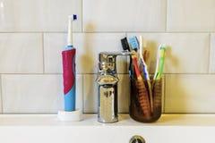 一个大家庭的口腔卫生的概念 在龙头和水槽的背景的许多不同的牙刷 库存图片