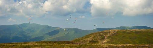 一个大小组的全景照片在天空的滑翔伞在山上 免版税图库摄影