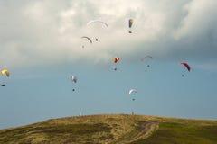 一个大小组滑翔伞在山上的天空飞行 免版税库存照片