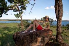 一个大岩石的Relaxing夫人 库存照片