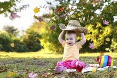 一个大帽子的美丽的愉快的女孩在秋天叶子期间的一个晴朗的草甸 免版税库存照片