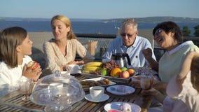 一个大愉快的家庭吃在开放大阳台的晚餐在房子的屋顶 股票录像