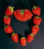一个大成熟莓果红色草莓的心脏在一黑暗的backgro的 免版税库存图片